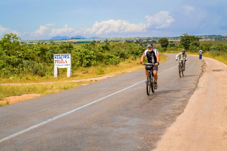 road cycling: Pilila, Zambia - March 31, 2015: Man riding bicycle on the road in the countryside of Zambia. Editorial