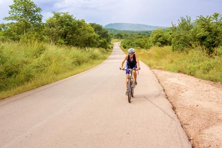 road cycling: Chongwe, Zambia - April 1, 2015: Young woman on bicycle is cycling in Zambia near Chongwe.