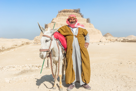 djoser: Saqqara, Egypt - December 31, 2014: Local man with donkey in front of step pyramid of Djoser. The first Egyptian Pyramid of Pharaoh Djoser 27 th century BC is situated in the necropolis of Saqqara, its stepped pyramid, actually at restoration.