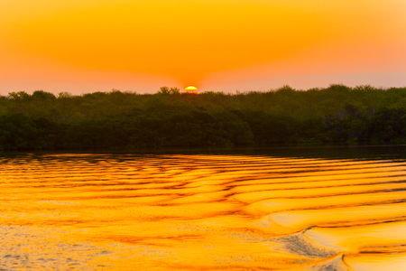 colrful: Picturesque sunrise over Santa Cruz island in Galapagos is turning the ocean color in gold Stock Photo