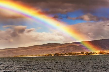 shorelines: Rainbow and the coastline of Kauai island of Hawaii as seen from the ocean. Stock Photo
