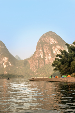 Yangshuo, China - October 1, 2008: Boats on Li river near Yangshuo, Guangxi province, China. Picturesque Karst mountains along the river and people camping at the river bank.