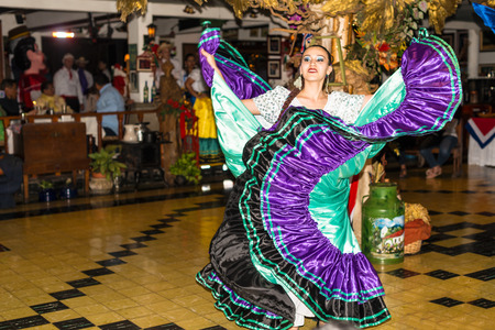 San Jose, Costa Rica - November 11, 2016: Young local girl wearing typical costume dancing lo Costa Rican folk music in the show at the restaurant in San Jose. Editorial