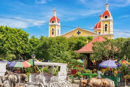 Granada, Nicaragua - November 20, 2016: Central Park and the towers of Granada Cathedral on the background. It is a neoclassical Catholic cathedral located in Granada. The church is the main temple of the Roman Diocese of Granada.