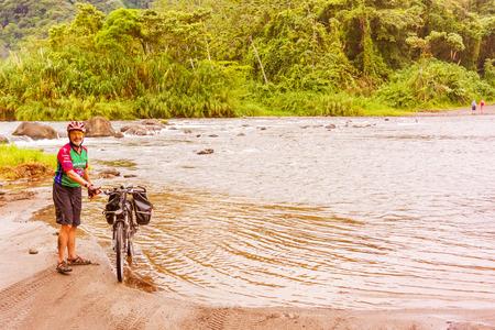 Guanacaste Province, Costa Rica - November 14, 2016: Travelling cyclist crossed the river Cano Negro near Rancho Margot in Costa Rica. Editorial
