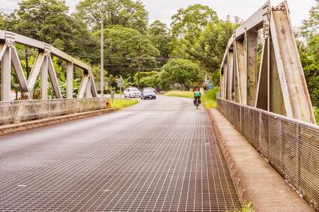Aguas Zarcas, Costa Rica - November 13, 2017: Man, cycles through the bridge over Rio Cano in Costa Rica near Aguas Zarcas.