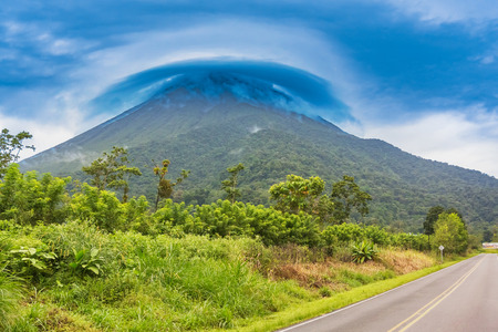 Picturesque view at the volcano Arenal peak covered in clouds as seen from the road near La Fortuna.