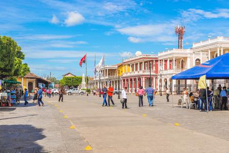 グラナダ、ニカラグア - 2016 年 11 月 20 日: 人々 は大聖堂広場にニカラグアのグラナダの町の歴史的な植民地建物の前を歩いてします。