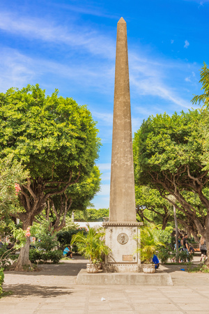 Granada, Nicaragua - Noivember 20, 2016:  Stone obelisk monument to Nicaraguan poet Ruben Darío was installed in 1966 on the 50th anniversary of his death. Parque Central is the main square and the historic heart of Granada, Nicaragua. Editorial