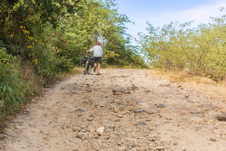 Rio Humuya, Honduras - November 28, 2016: Travelling thru mountains in Honduras. Cyclist walking with bicycle on a steep dirt road v 280 near Rio Humuya Editorial