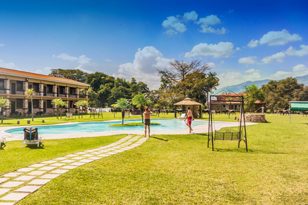 Chiquimula, Guatemala - December 2, 2016: People at the swimming pool and the buildings in Grand Caporal hotel in Guatemala.