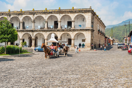 Antigua, Guatemala - December 06, 2016: People are seen walking and riding horse carriages on the cobblestone streets by the main Plaza of Antigua, Guatemala.