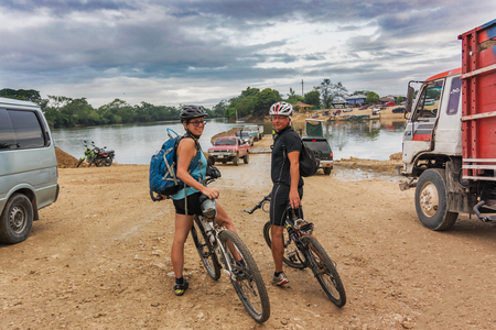 Sayaxche, Guatemala - December 14, 2016: Cyclists are crossing the river called Rio de la Pasion on a ferry in a small town of Sayaxche in Guatemala.