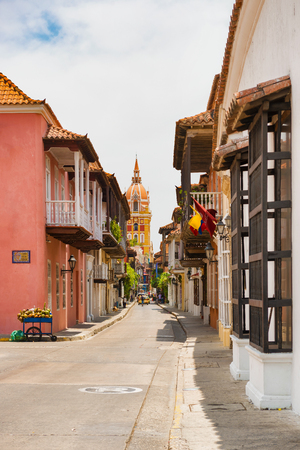 Cartagena, Colombia - March 26, 2017: Tourists walking old colonial street withMetropolitan Cathedral Basilica of Saint Catherine of Alexandria at the background in Cartagena, Colombia.