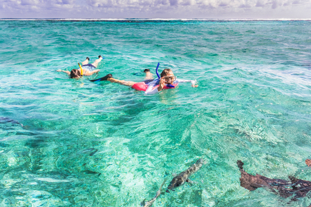 People are snorkeling at the reef near Caye Caulker in Belize. It is a small island near Ambergris Caye. The island is very popular with divers because of its close proximity to the Belize Barrier Reef. Redakční