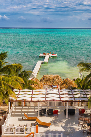 december 25: Caye Caulker, Belize - December 25, 2016: Aerial view at wooden pier dock with tourists and picturesque, relaxing ocean view at Caye Caulker Belize Caribbean.