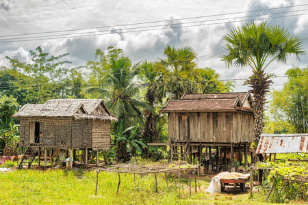 Typical Cambodian houses at the countryside road near Kampong Thom in Cambodia.