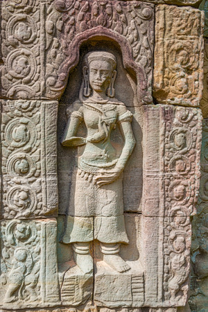 Carved dancers on the wall in Ta Som the temple at Angkor, Cambodia, built at the 12th century. The temple was left largely unrestored, with numerous trees and other vegetation overgrowing the ruins. Stock Photo