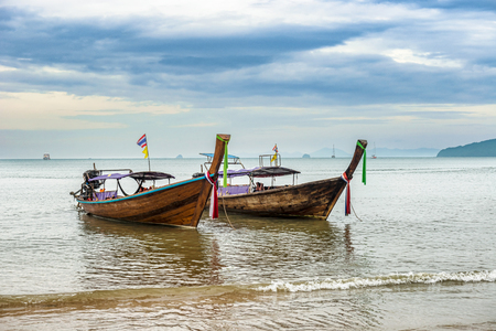 Sunrise over the main beach in Ao Nang resort town of the coastal province of Krabi, Thailand with number of longtail boats which offer access to other beaches on the mainland and on nearby islands.