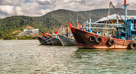 The colorful fishing boats at the anchor of the coast in Penang, Malaysia.