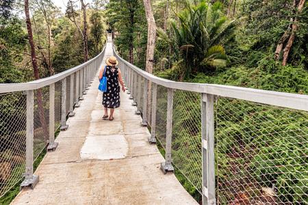 George Town, Penang, Malaysia: Woman crossing the hanging bridge in the Habitat  Penang Hill on Canopy Walk Penang, Malaysia.