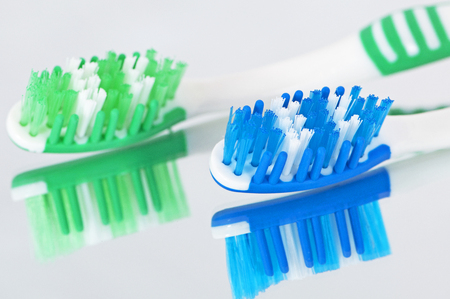 Toothbrushes on a reflective surface