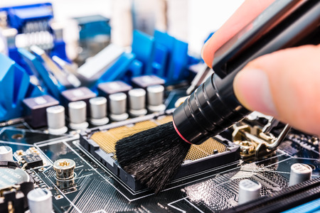 computer protection: Cleaning of the computer with brush Stock Photo