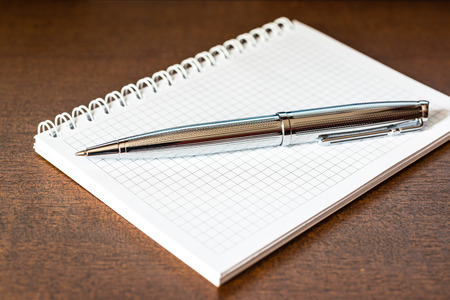 Notebook with a pen on the table photo
