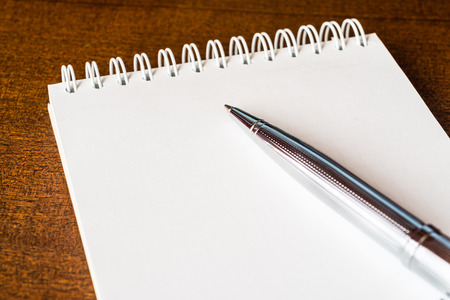 scribe: Empty notebook with a pen on the table