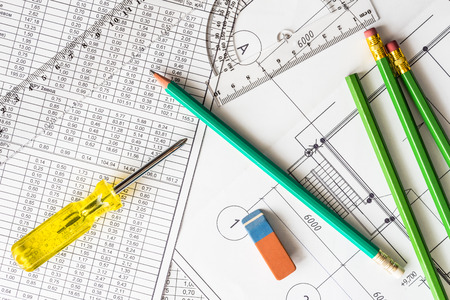 architectural drawings: Architectural drawings, a screwdriver with tools for sketching on the table