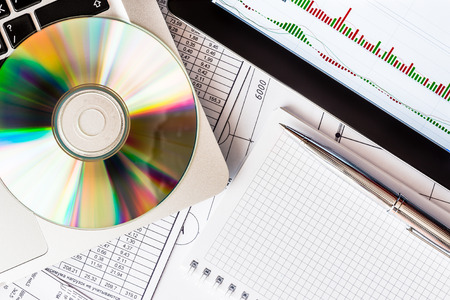indices: Stock exchange indices, a tablet and a laptop on the table with a optical disk with a data
