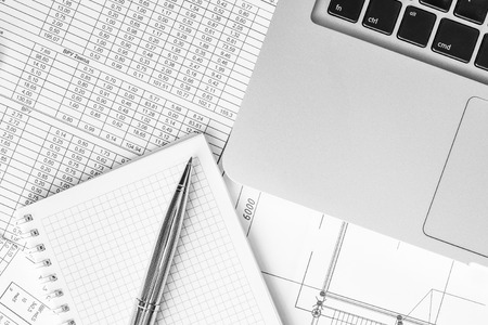 note pad: Preparation of financial statements for the project, a notebook with a pen on the table. In black and white tones