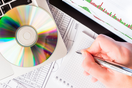 indices: Analysis of the stock exchange indices, a tablet and a laptop on the table with a optical disk with a data