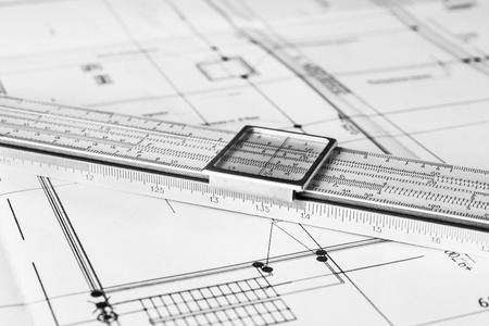 construction equipment: Schemes and slide rule on the table. Angle view, in black and white tones