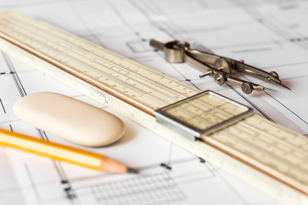 arhitecture: Preparation for drafting papers, the tools and schemes on the table. Angle view, focus on a compass Stock Photo