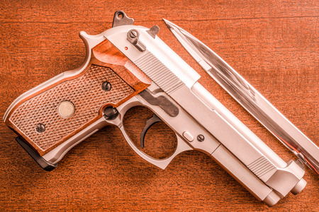 9mm ammo: The knife and the pistol on the table. Top view, in red tones Stock Photo