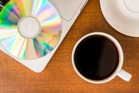 optical disk: Work in the office, coffee cup and a plate with an optical disk with laptop on the wooden table
