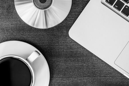 optical disk: Work in the office, coffee cup and a plate with an optical disk with laptop on the wooden table. In black and white tones