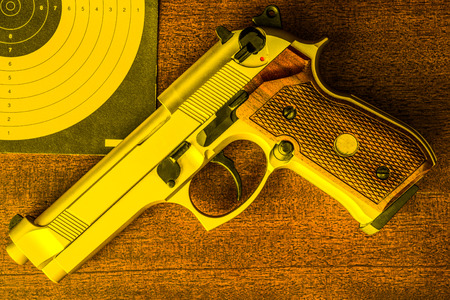 9mm ammo: Target shooting, the gun and the target on the table. Top view, in yellow tones Stock Photo