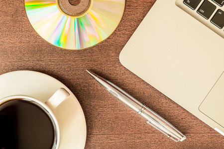 optical disk: Work in the office, coffee cup and a plate with an optical disk with laptop on the wooden table. In retro tones