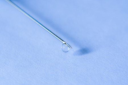 Medicine flows from the syringe and spread out. Angle close up view in blue tones photo