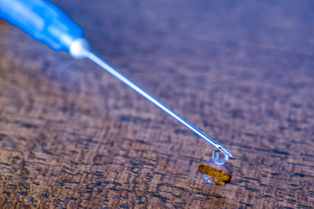 Medicine flows from the syringe and spread out. Angle close up view photo