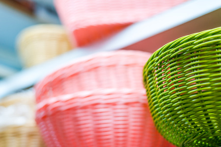 shelf: Colored wicker basket on the shelf Stock Photo