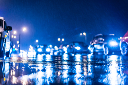 estado del tiempo: Rainy day in the city at night, stream of cars on the road. In blue tones Foto de archivo