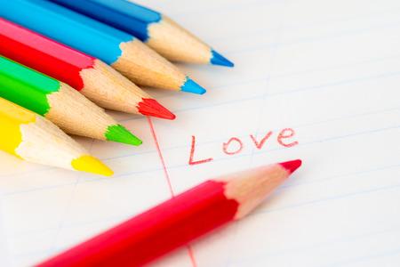 ノートの上に横たわる着色された鉛筆、赤鉛筆でノートに書かれた単語の愛