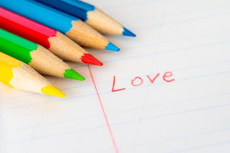 색깔 된 연필로 노트북에 쓰여진 단어 사랑 스톡 콘텐츠