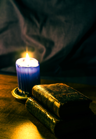Bible and old books and candle on a wooden table. Focus on the old books, image in yellow-blue toning