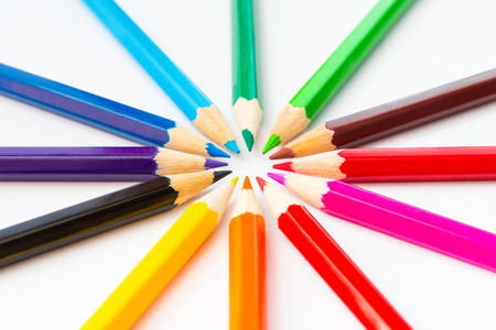 Colored pencils in a circle on the paper. Angle view, in soft light Standard-Bild