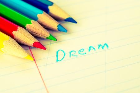 色鉛筆とノートに書かれて単語の夢。黄-青の調色のイメージ 写真素材
