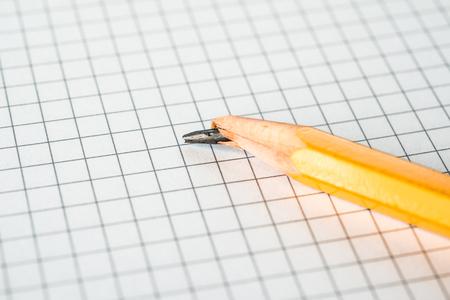 メモ帳の上に横たわる折れた鉛筆